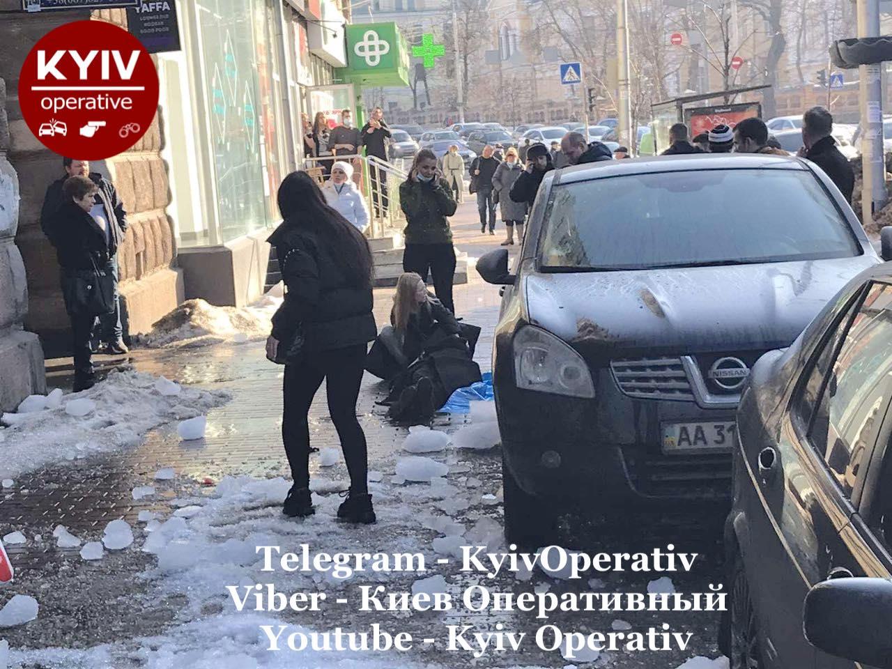 В центрі Києва на дівчину впала величезна брила льоду: її намагаються врятувати пішоходи (фото)