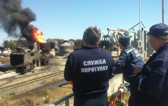 Фото: спасатели наблюдают за пожаром на нефтебазе