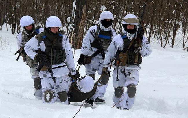 Фото: поранений боєць ЗСУ на ношах (facebook.com/ato.news)
