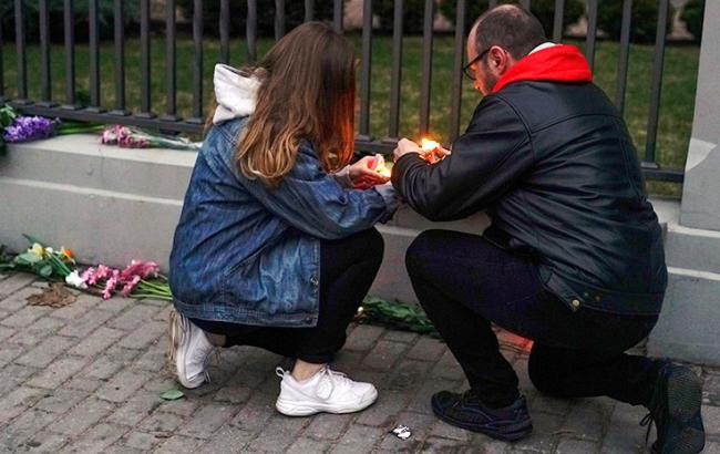 Фото: Люди несут цветы к посольству