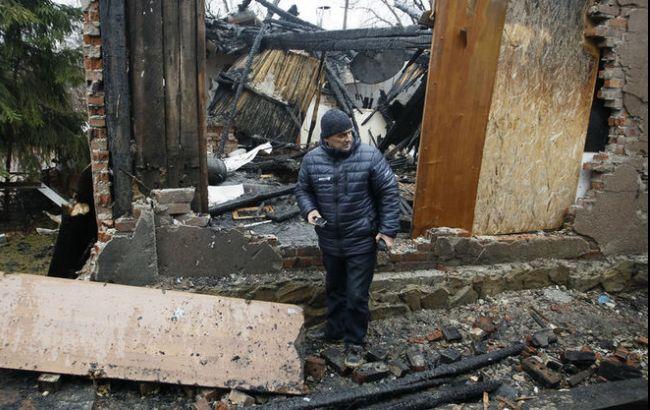 Фото: чоловік на фоні розбомбленого будинку