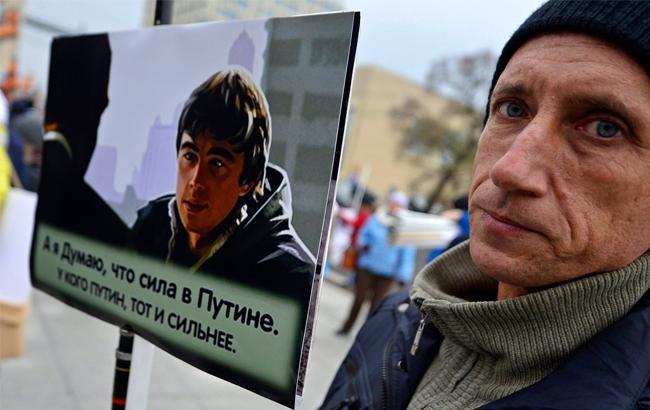 Фото: Мужчина с плакатом про Путина (twitter.com)