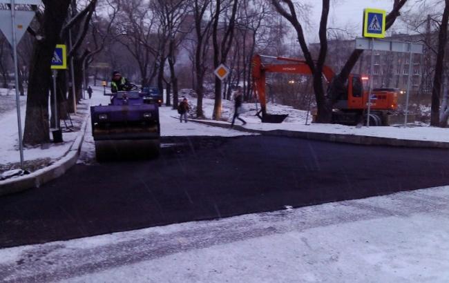 Фото: Киевские коммунальщики стелят асфальт под снегом (VL.ru)