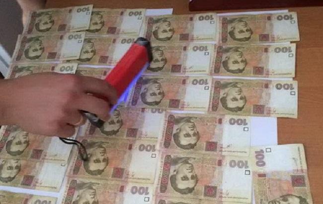 Фото: поліцейського затримали з готівкою в робочому кабінеті