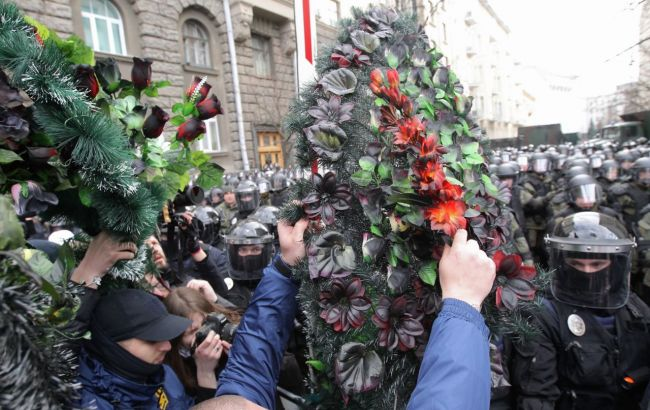 В Киеве протестующие обложили кордон силовиков похоронными венками